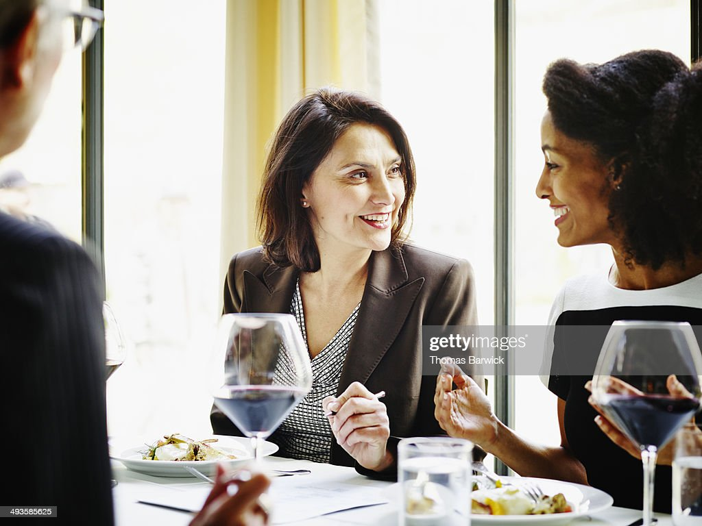 Smiling female executives meeting over lunch