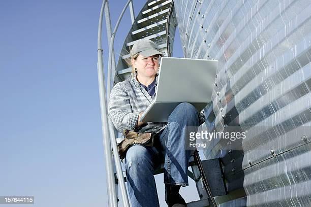 Souriant femme agriculteur sur les escaliers de un silo