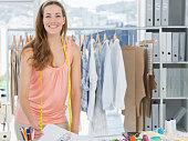 Portrait of a smiling beautiful female fashion designer working in studio