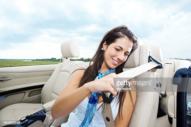 Smiling female fastening her seat belt.