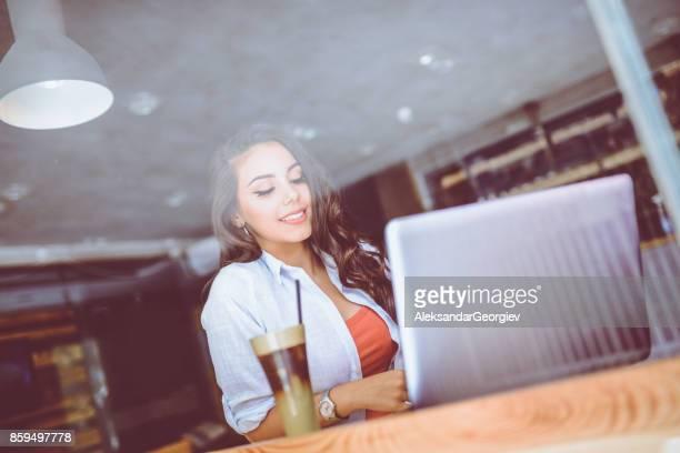 Smiling Female Freelancer Working in her Favorite Cafe in Morning