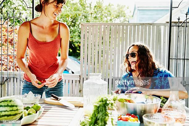 Smiling female friends preparing for summer dinner