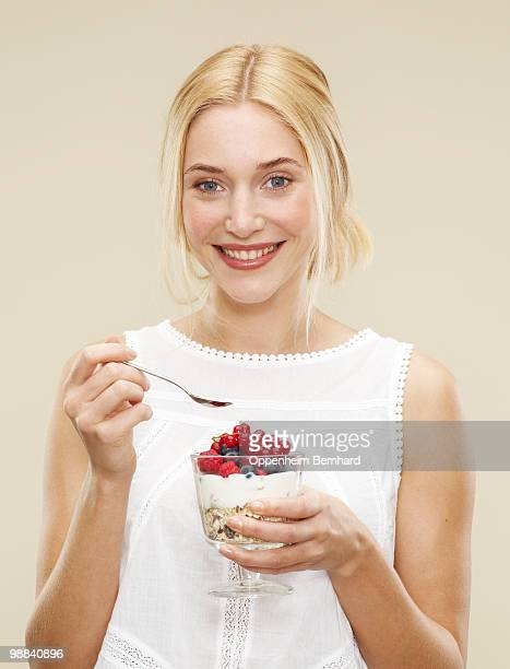 smiling female holding bowl of cereal and berries
