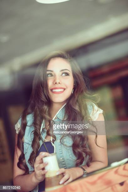 Smiling Female Listening Music and Drinking Coffee in Cafe