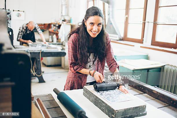 Smiling female lithograph worker using roller at printing house