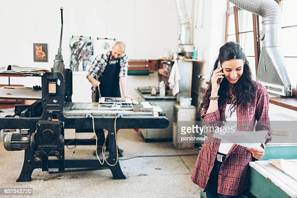 Smiling female lithography worker using smart phone in printing house