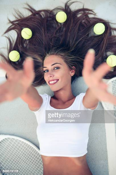 Smiling Female Lying on Tennis Court and Reaching to the Camera