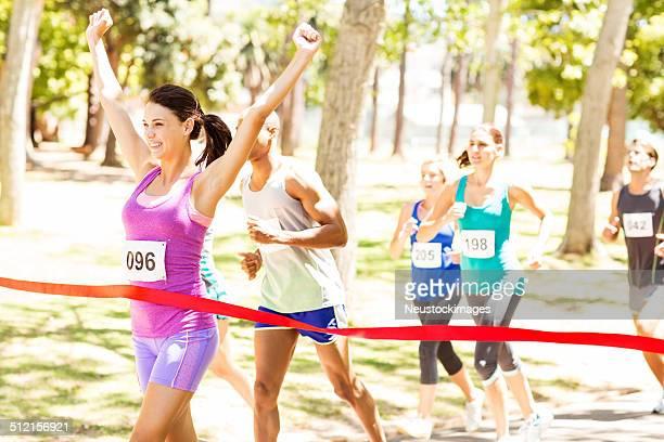 Lächelnd weiblichen Marathon-Läufer Kreuzung Ziellinie
