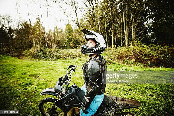 Smiling female motorcyclist resting during dirt bike ride with friends