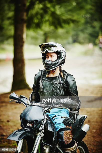 Smiling female motorcyclist sitting on dirt bike before riding with friends