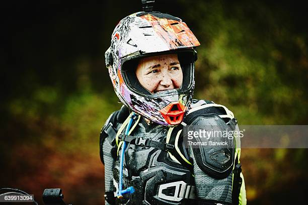 Smiling female motorcyclist with muddy face in discussion with friends while riding dirt bike