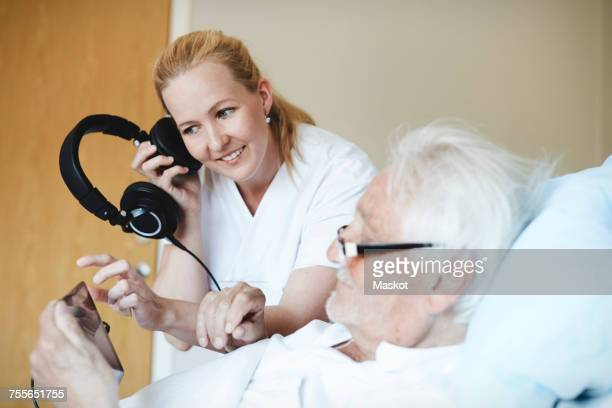 Smiling female nurse listening music through headphones while using digital tablet in hospital ward