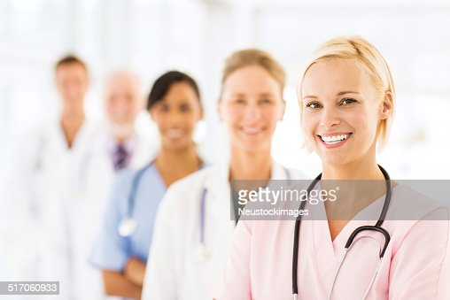 Smiling Female Nurse With Medical Team