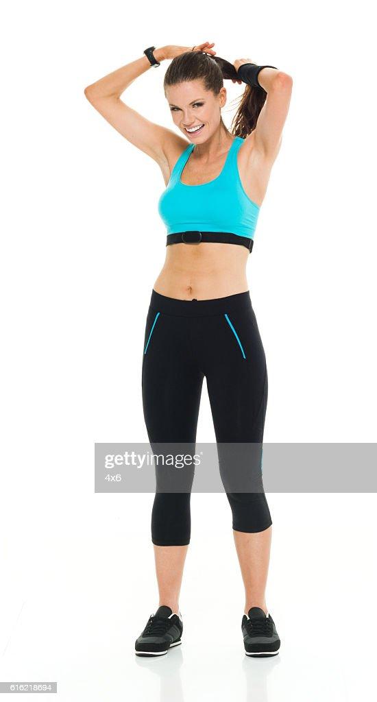 Smiling female runner tying her hair : Stockfoto