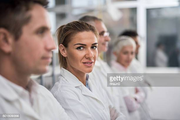 Smiling female scientist with her team in laboratory.