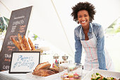 Female Bakery Stall Holder At Farmers Fresh Food Market, Smiling To Camera