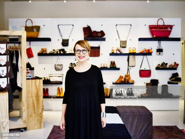 Smiling female shop owner standing in boutique