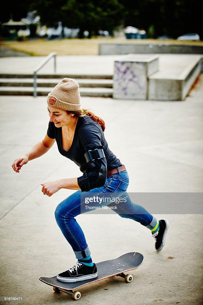 Smiling female skateboarder riding skateboard