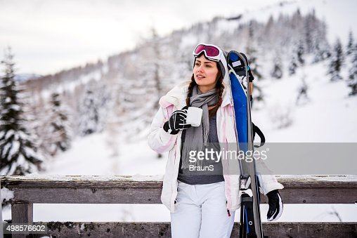 Smiling female skier taking a coffee break from skiing.