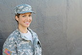Smiling female soldier standing with copy space.