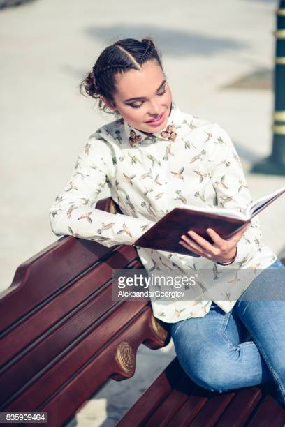 Smiling Female Student Reading Book on the City Bench