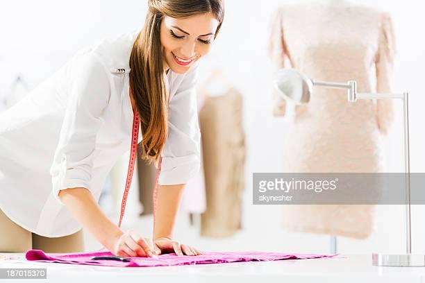 Sorridente Mulher alfaiate no trabalho.