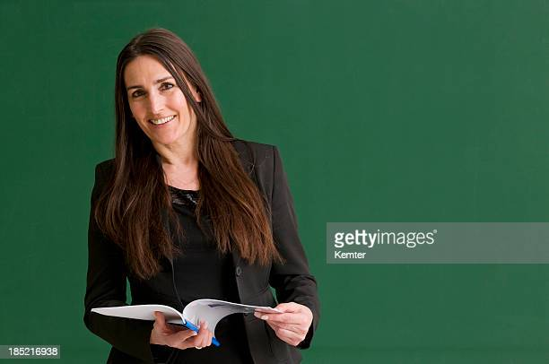 Smiling female teacher against a green chalkboard.