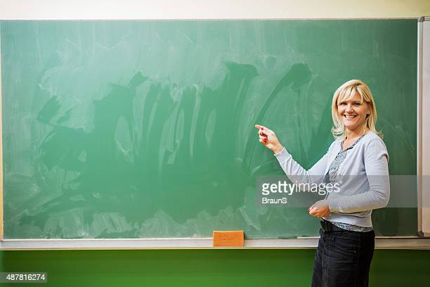 Smiling female teacher pointing at blackboard. Copy space.