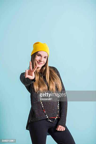 Smiling female teenager showing victory-sign wearing yellow cap