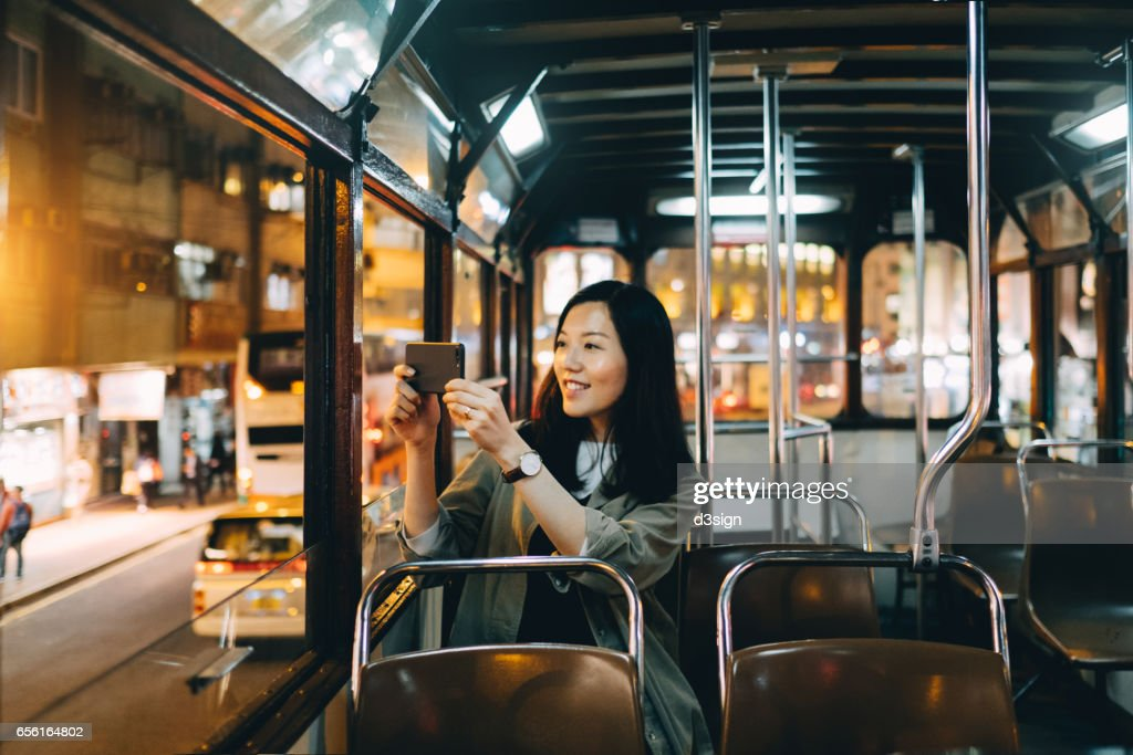 Smiling female tourist taking pictures of night scene with smartphone on a tram ride in Hong Kong : Stock Photo