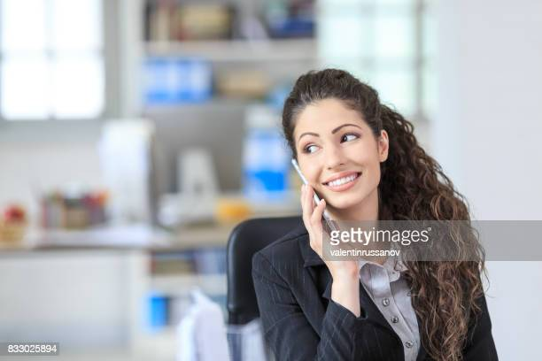 Smiling female white collar worker talking on smart phone