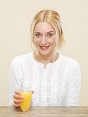 smiling female with glass of fresh orange juice