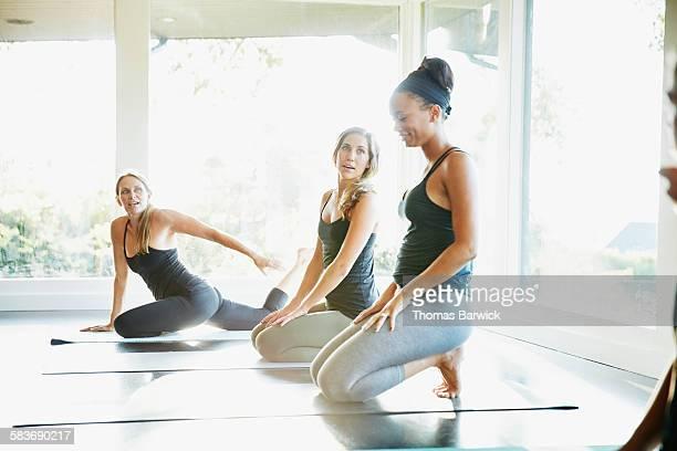 Smiling female yoga instructor kneeling on mat