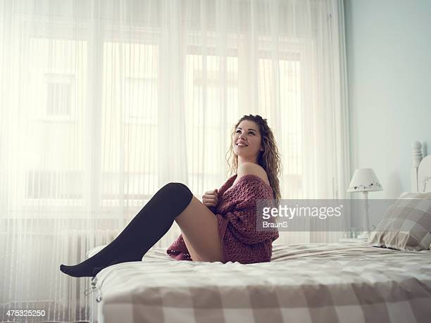 Smiling feminine woman in bedroom looking up.