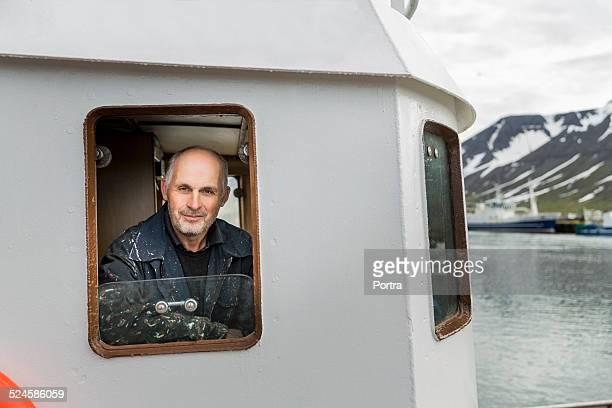 Smiling fisherman sitting in fishing boat