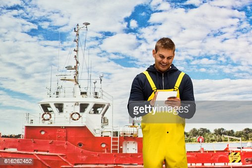 Smiling fisherman using tablet at the fishing boat : Stock Photo