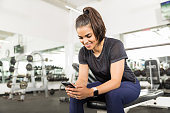 Smiling fit woman using smart phone while sitting on bench in health club