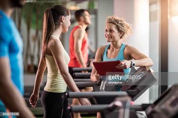 Smiling fitness trainer talking to young woman in a gym.
