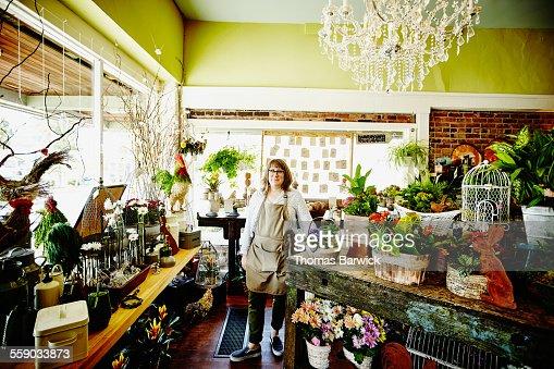 Smiling floral shop owner standing in flower shop