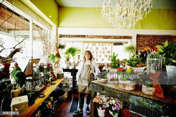 Smiling floral shop owner standing in flower shop