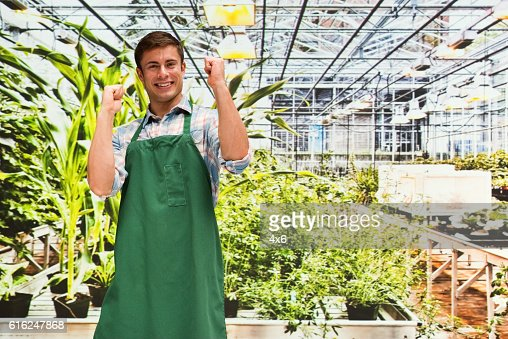 Smiling florist cheering in greenhouse : Stock Photo