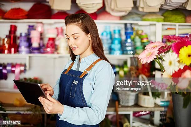 Smiling florist using digital tablet in flower shop