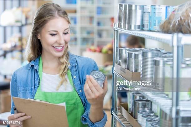 Lächelnde Bankschecks Essen freiwillige Ablaufdaten auf Konserven