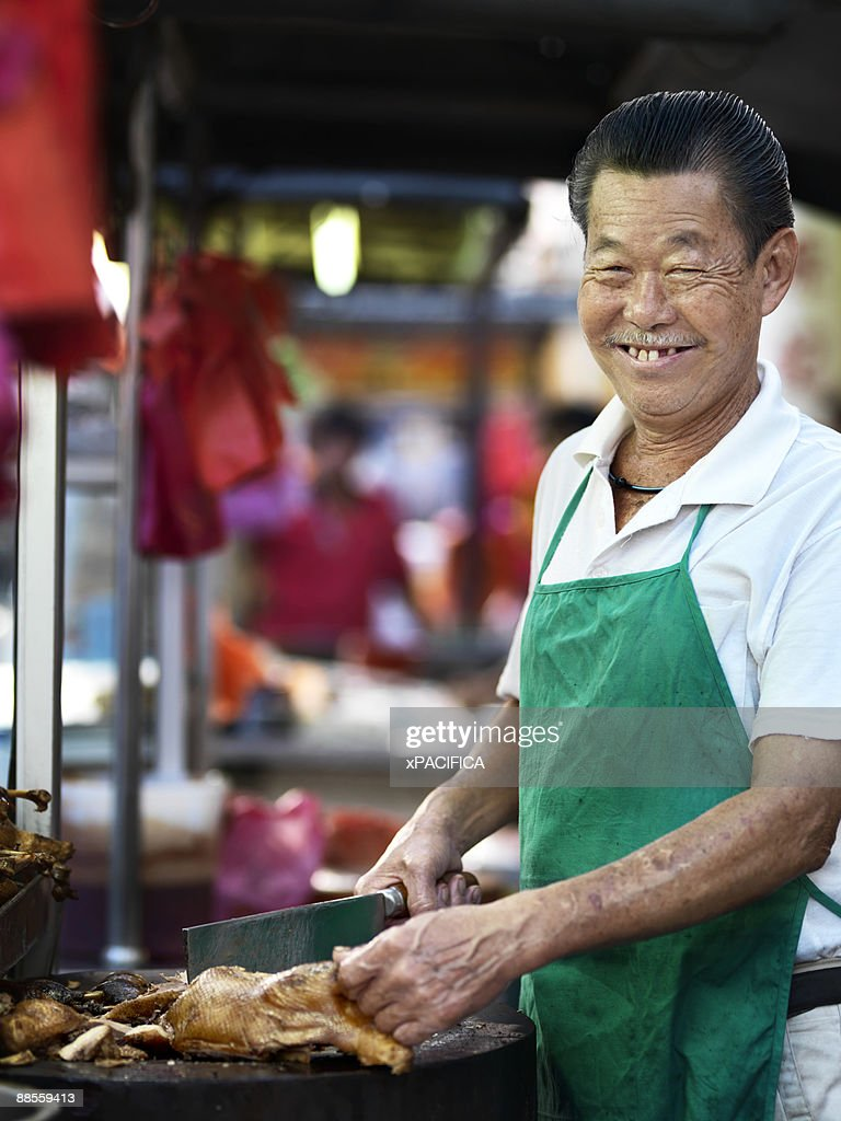A smiling food vendor preparing duck. : Stock Photo