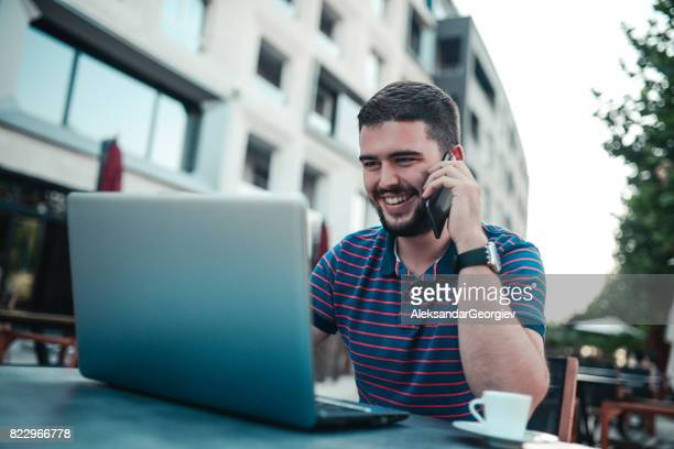 Smiling Freelancer Working and Talking on the Phone at his Favorite Coffee Place