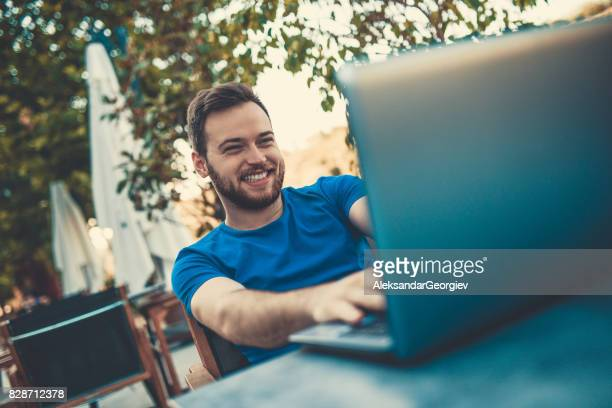 Smiling Freelancer Working at his Favorite Coffee Place