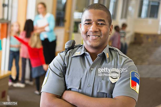 Smiling friendly police officer providing security on school campus