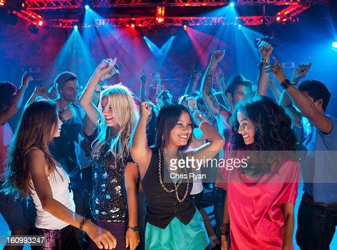 Smiling friends dancing on dance floor of nightclub