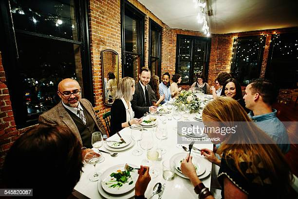 Smiling friends dining together at dinner party