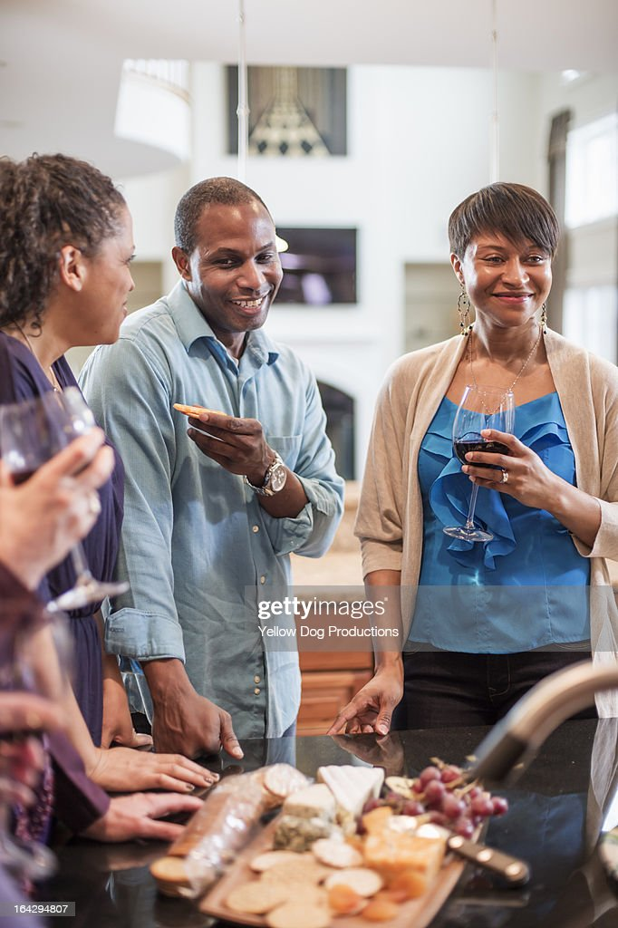 Smiling Friends Drinking and Eating at a Party : Stock Photo